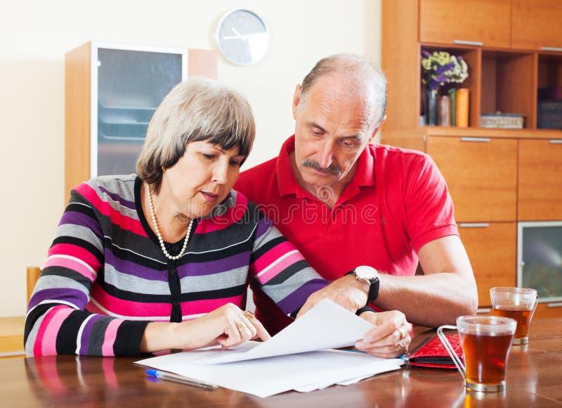 Mogna par som läser det finansiella dokumentet royaltyfri foto