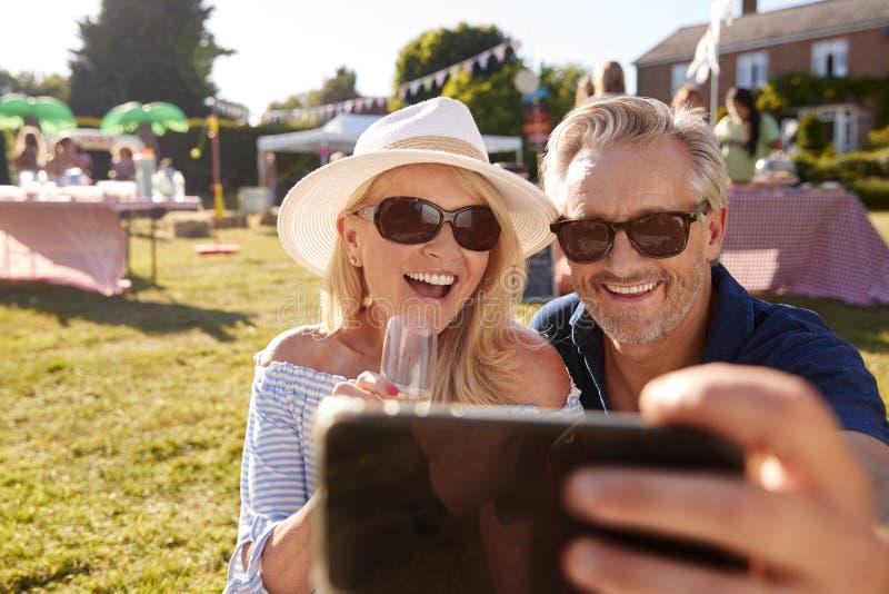 Mogna par som sitter på filten på sommarträdgårdstora festen som tar Selfie på mobiltelefonen royaltyfria bilder
