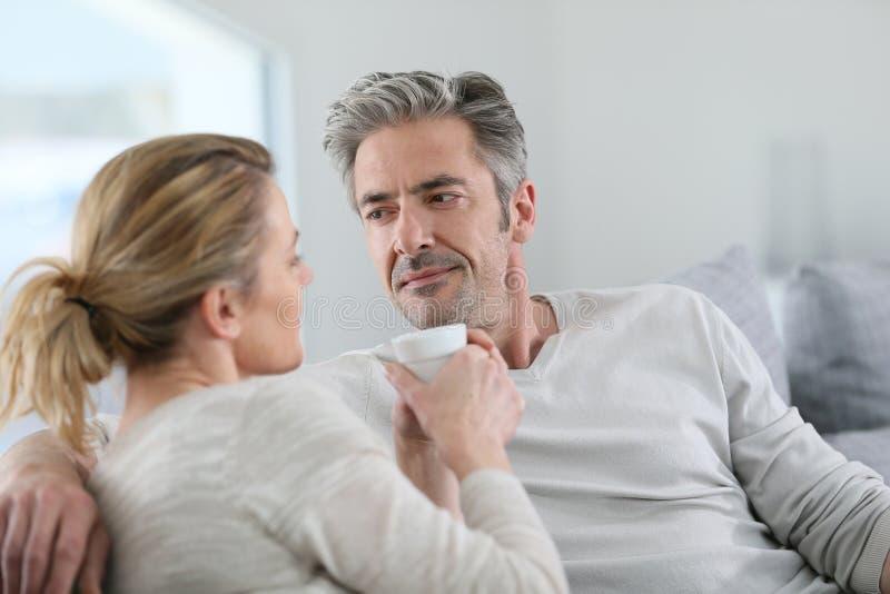 Mogna par som talar och dricker kaffe royaltyfri fotografi