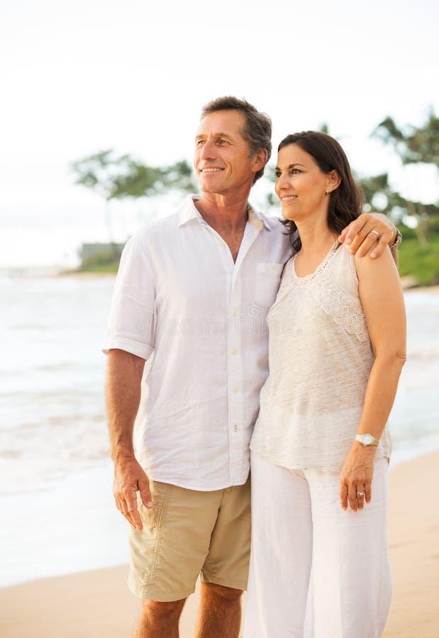 Mogna par som tycker om solnedgång på stranden arkivfoto