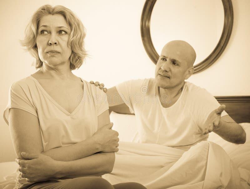 Mogna par som ut sorterar förhållanden i säng royaltyfri bild