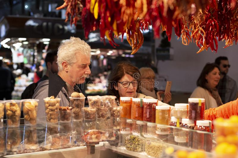 Mogna par som väljer kryddor på den berömda marknaden i Barcelona, Catalonia, Spanien 2019-04-30 royaltyfria foton