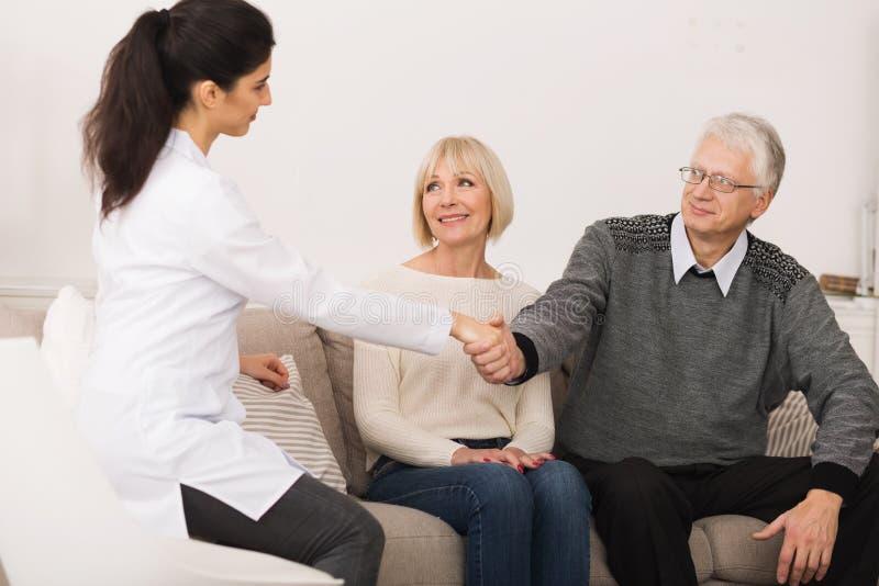 Mogna par som välkomnar sjuksköterskan During Home Visit royaltyfri bild