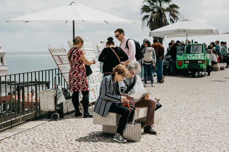 Mogna parsammanträde på en bänk och att se en översikt i Lissabon i Portugal arkivbilder