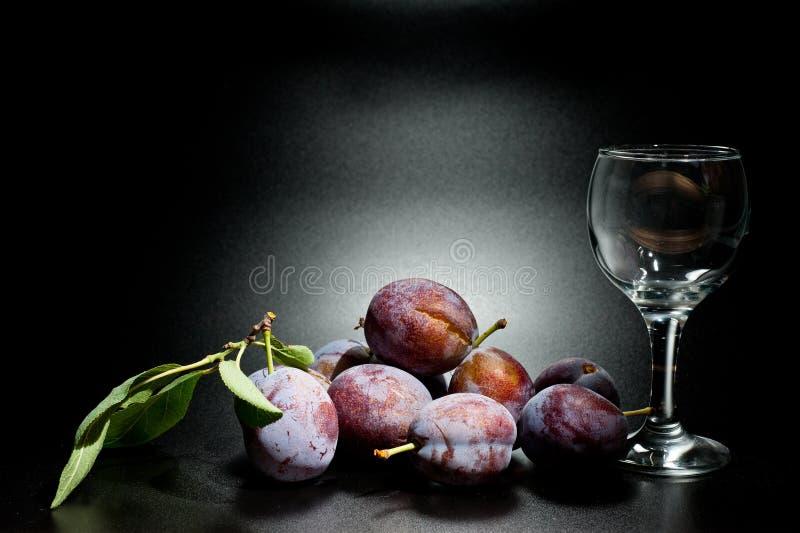 Mogna plommoner och saftig skottnärbild på en mörk bakgrund och ett exponeringsglas av vin royaltyfri foto