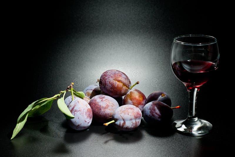 Mogna plommoner och saftig skottnärbild på en mörk bakgrund och ett exponeringsglas av vin arkivfoto