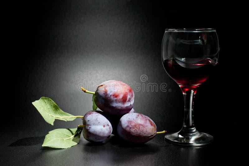 Mogna plommoner och saftig skottnärbild på en mörk bakgrund och ett exponeringsglas av vin fotografering för bildbyråer