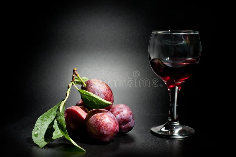 Mogna plommoner och saftig skottnärbild på en mörk bakgrund och ett exponeringsglas av vin royaltyfria foton