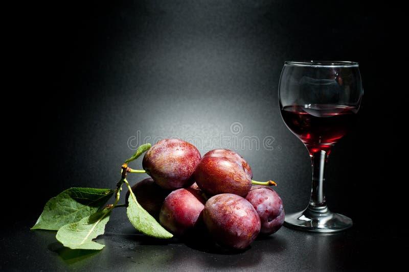 Mogna plommoner och saftig skottnärbild på en mörk bakgrund och ett exponeringsglas av vin arkivfoton