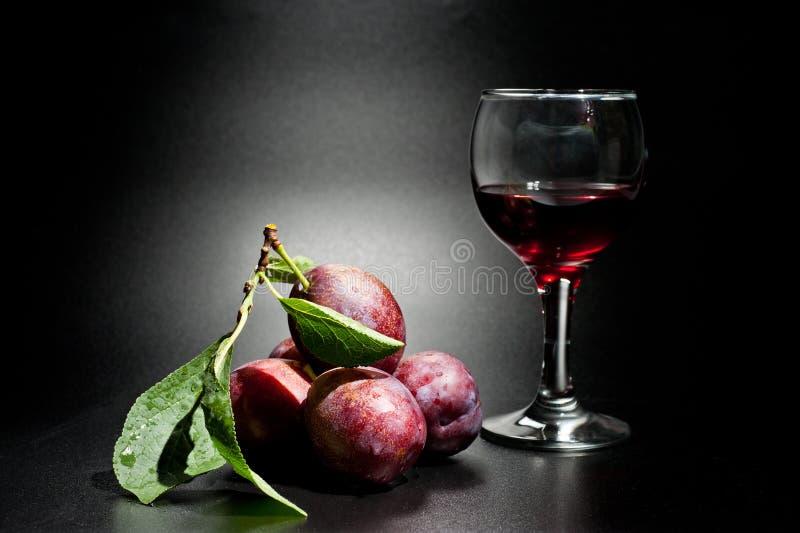 Mogna plommoner och saftig skottnärbild på en mörk bakgrund och ett exponeringsglas av vin royaltyfri fotografi