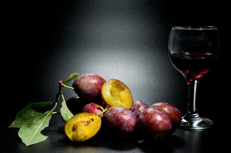 Mogna plommoner och saftig skottnärbild på en mörk bakgrund och ett exponeringsglas av vin royaltyfri bild