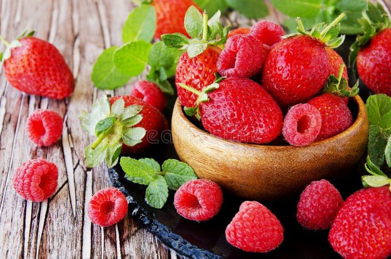 Mogna röda hallon och jordgubbar i träbunken, selektiv fokus royaltyfri foto