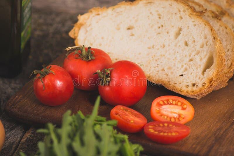 Mogna röda tomater och bröd royaltyfri foto