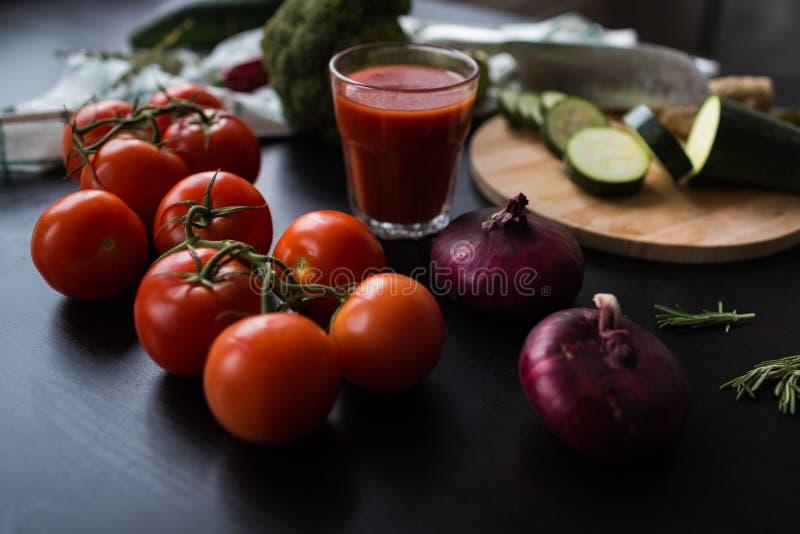 Mogna röda tomater och stora röda lökar ligger på en svart stilfull tabell i bakgrunden ser vi ett exponeringsglas av tomaten royaltyfria bilder