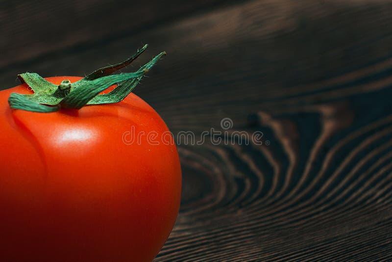 Mogna röda tomater på en trätabell arkivfoton
