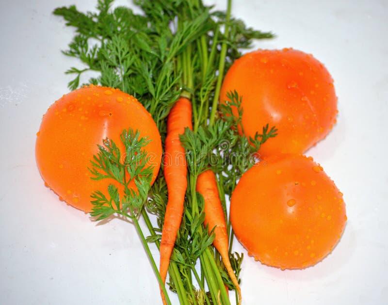Mogna saftiga orange tomater och morötter med gröna sidor ligger på en vit tabell, naturliga vitaminer royaltyfria bilder