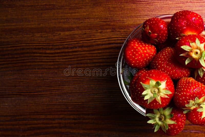 mogna saftiga röda jordgubbar är i en glass bunke på trätabellen royaltyfri fotografi