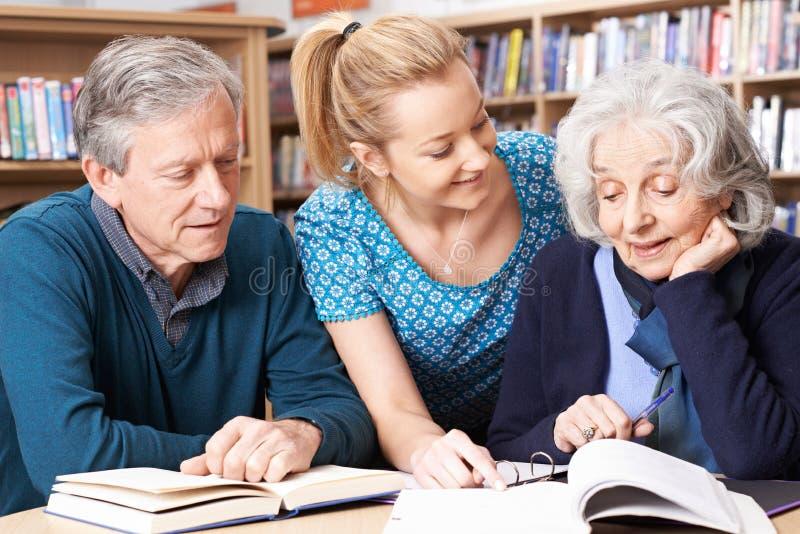 Mogna studenter som arbetar med läraren In Library arkivfoton