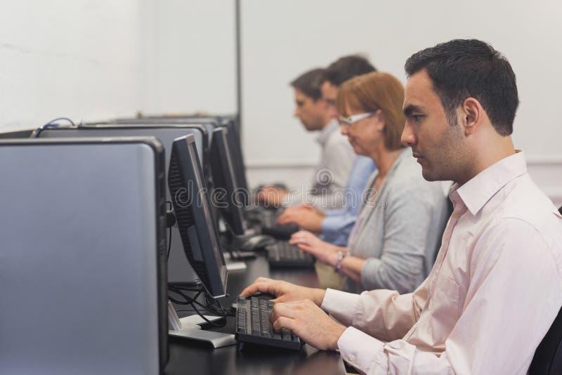 Mogna studenter som sitter i datorgrupp arkivbild
