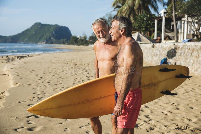 Mogna surfare på stranden arkivfoto
