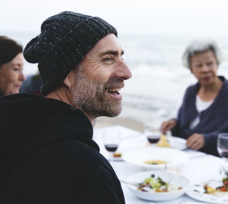 Mogna vänner som dricker vin på stranden arkivfoton