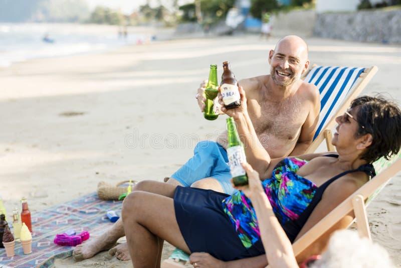 Mogna vänner som har öl på stranden royaltyfria foton