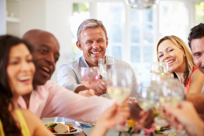 Mogna vänner som sitter runt om tabellen på matställepartiet fotografering för bildbyråer