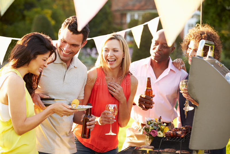 Mogna vänner som tycker om den utomhus- sommargrillfesten i trädgård arkivbild