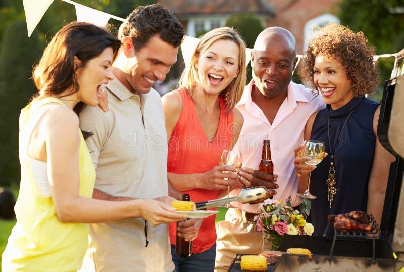 Mogna vänner som tycker om den utomhus- sommargrillfesten i trädgård royaltyfri fotografi