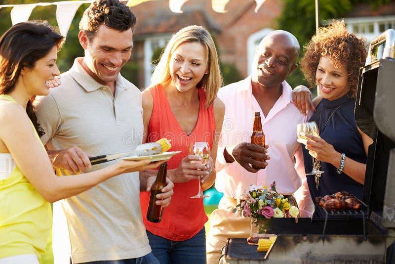 Mogna vänner som tycker om den utomhus- sommargrillfesten i trädgård arkivfoto