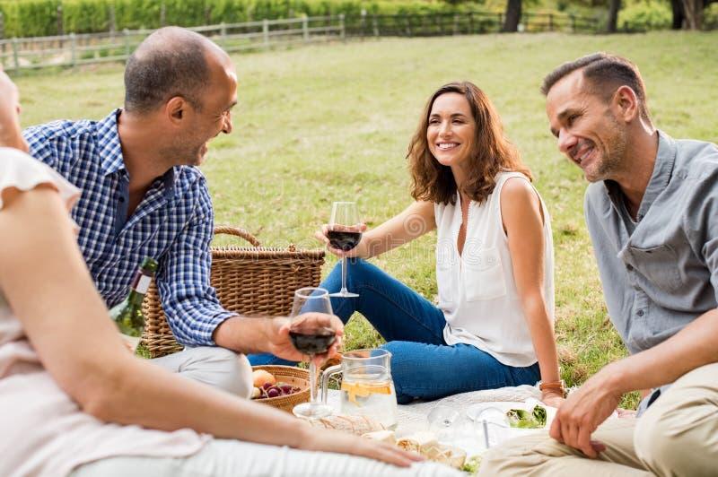 Mogna vänner som tycker om picknicken royaltyfria foton