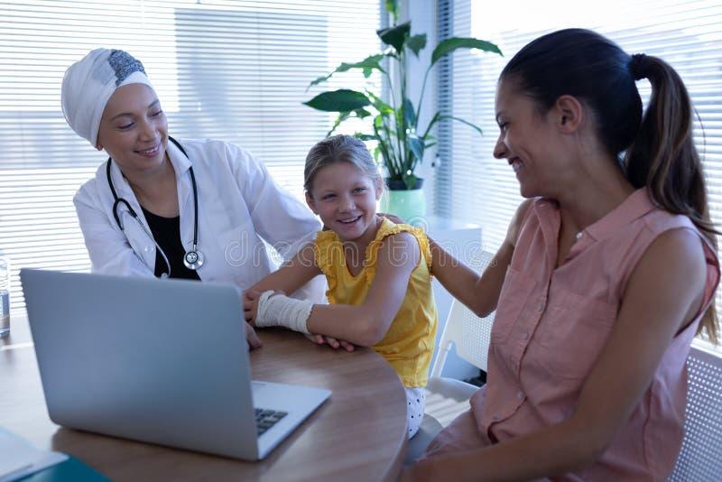 Mognad kvinnlig doktor och moder som talar med flickapatienten i klinik fotografering för bildbyråer