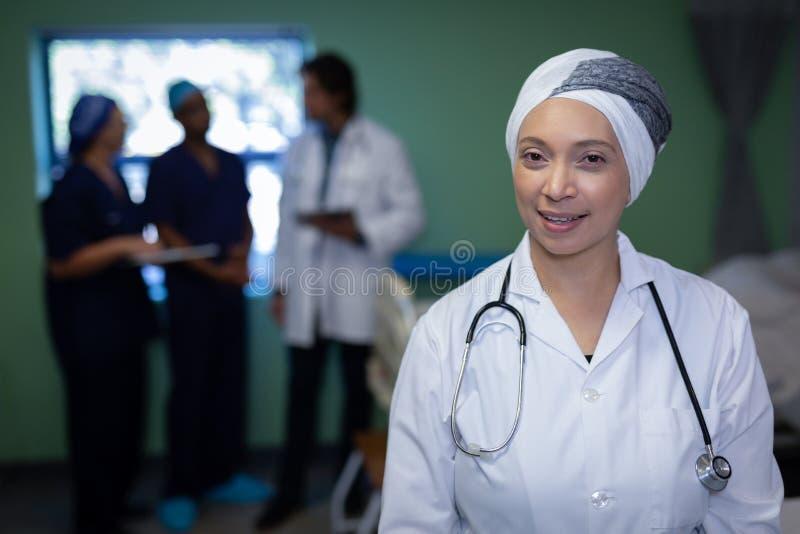 Mognad kvinnlig doktor som ler i klinik på sjukhuset arkivbild