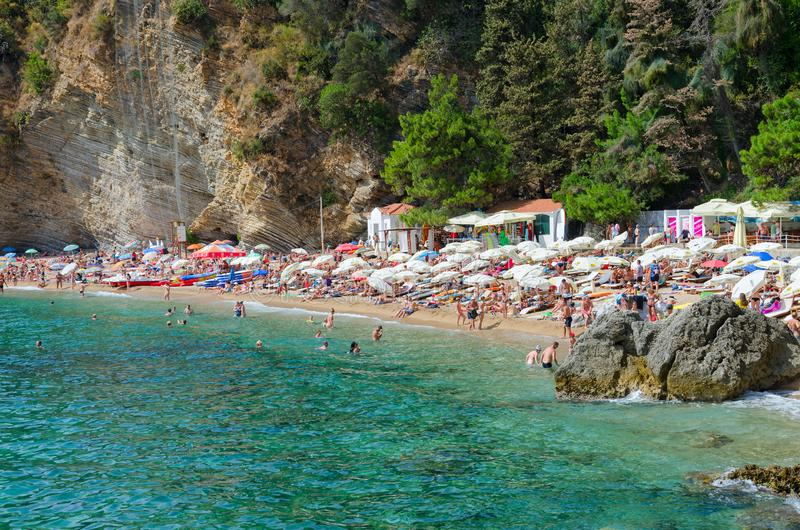 People relax on Mogren beach in popular resort town of Budva, Montenegro. BUDVA, MONTENEGRO - SEPTEMBER 7, 2017: Unidentified people relax on Mogren beach in stock photos