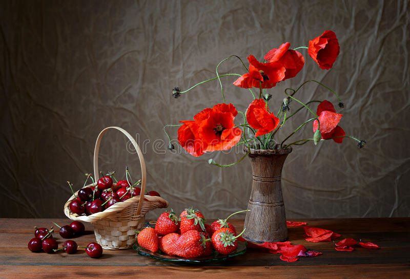 Mohnblume in einem keramischen Vase, in den Kirschen und in den Erdbeeren stockbilder