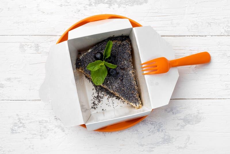 Mohnkuchen mit Blaubeeren im Papierkasten lizenzfreies stockbild