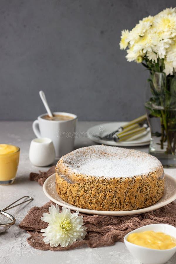 Mohnsamenkuchen mit Zuckerpulver und Schmack mit einer Tasse Kaffee lizenzfreie stockfotos
