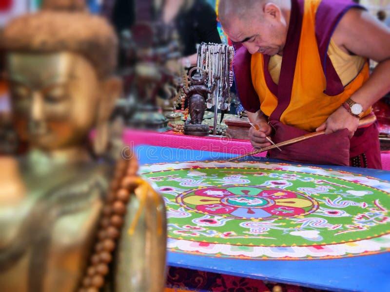 Moine bouddhiste créer le mandala de dessin avec le foyer sélectif de sables multicolores sur des mains photos libres de droits