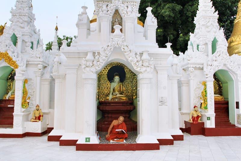 Moine bouddhiste priant à la pagoda 1 de Shwedagon de 5 endroits sacrés la pagoda d'or sacrée qui symbolisent le chant religieux photographie stock