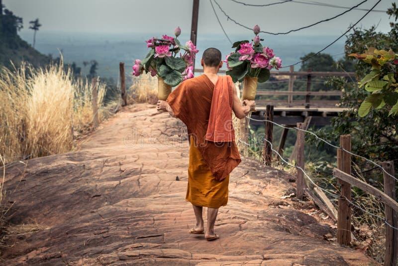 Moine thaïlandais avec des fleurs de lotus dans des ses mains marchant sur une route pierreuse chez Wat Phu Tok photos stock