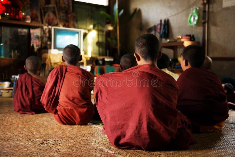 Moines bouddhistes appréciant l'exposition de TV photographie stock