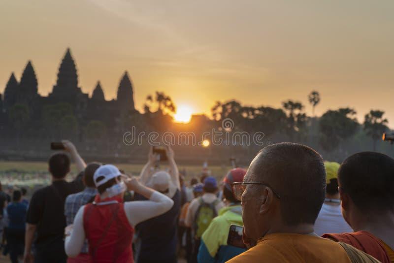 Moines bouddhistes et touristes au coucher du soleil chez Angkor Vat photographie stock libre de droits