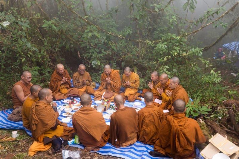 Moines bouddhistes priant en nature images stock