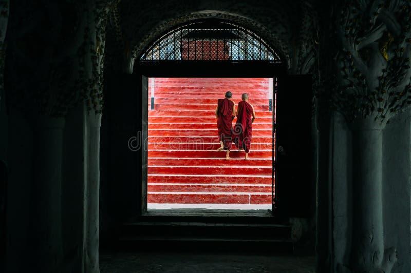2 moines marchant vers le haut des escaliers à Mandalay photographie stock libre de droits