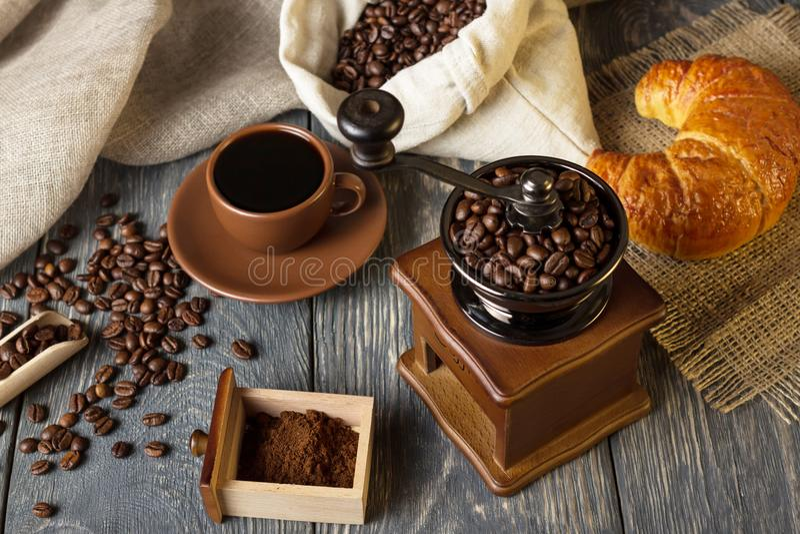 Moinho, borra de café e feijões manuais, bebida quente no copo imagens de stock