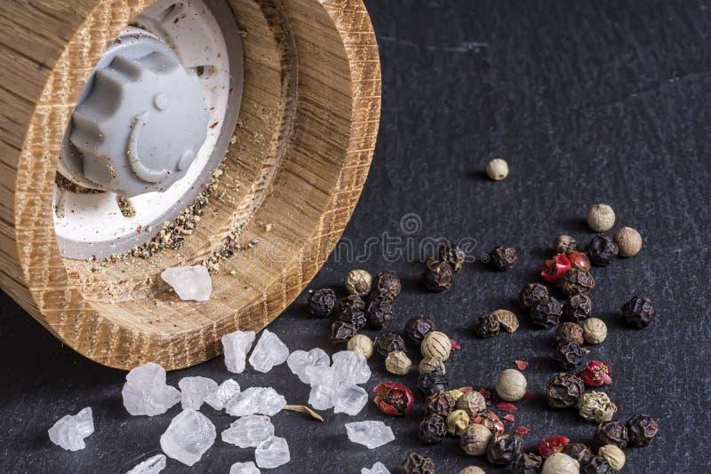 Moinho de pimenta, grões de sal do mar e de pimenta no fim escuro da superfície da pedra acima imagem de stock