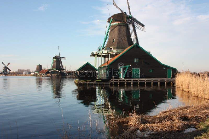 Moinho de vento antigo holandês construído da madeira estrutura típica dos Países Baixos ferramentas velhas do trabalho no rio na foto de stock