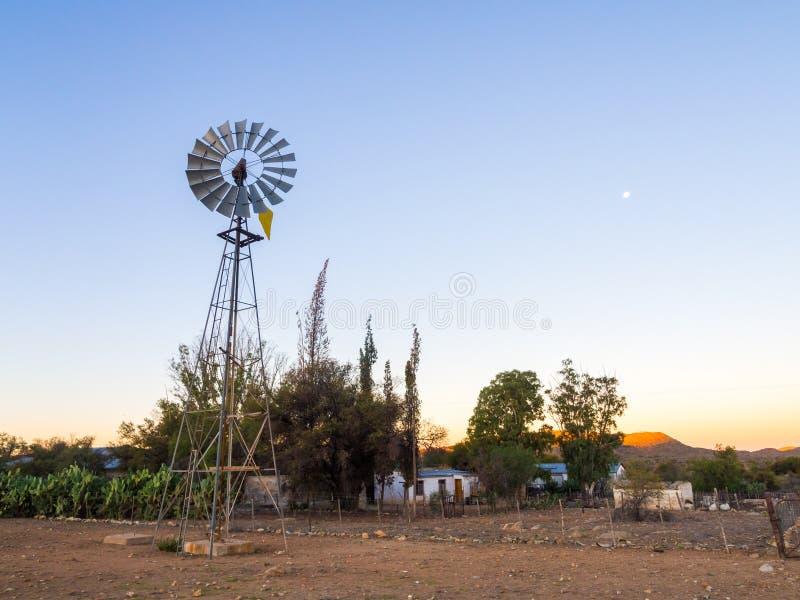 Moinho de vento ao lado de uma exploração agrícola, montanhas de Khomas, Namíbia fotos de stock royalty free