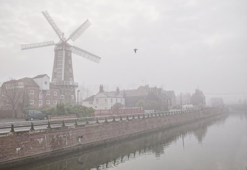 Moinho de vento ao lado de um rio enevoado imagem de stock