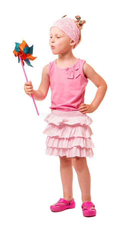 Moinho de vento de sopro da menina loura pequena bonito isolado no branco imagem de stock